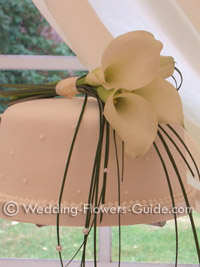 a cluster of white calla lilies used as a wedding cake topper