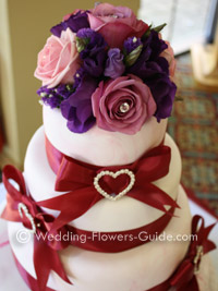 fresh roses and lisianthus arranged as a wedding cake topper