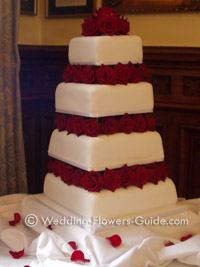 red roses placed inbetween each tier of a wedding cake