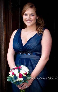 bridesmaid dressed in blue holding a coordinating posy bouquet