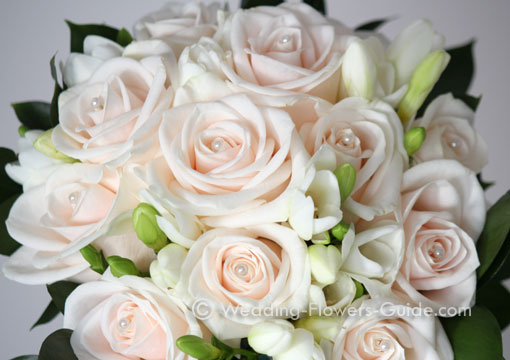 cream roses with a pearl pin in the centre