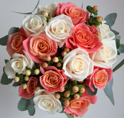 Bridesmaids handtied posy bouquet containing peach and cream roses.