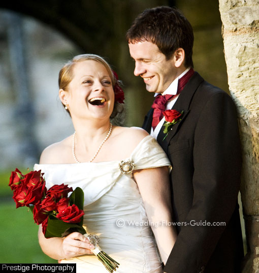 bride and groom photographed with red rose wedding flowers